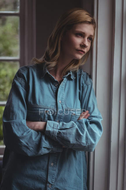 Thoughtful woman leaning on wall at home — Stockfoto