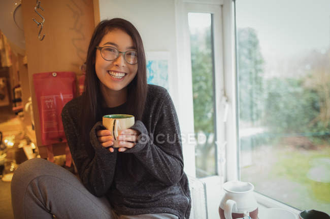 Retrato de mulher segurando uma xícara de café na cozinha em casa — Fotografia de Stock