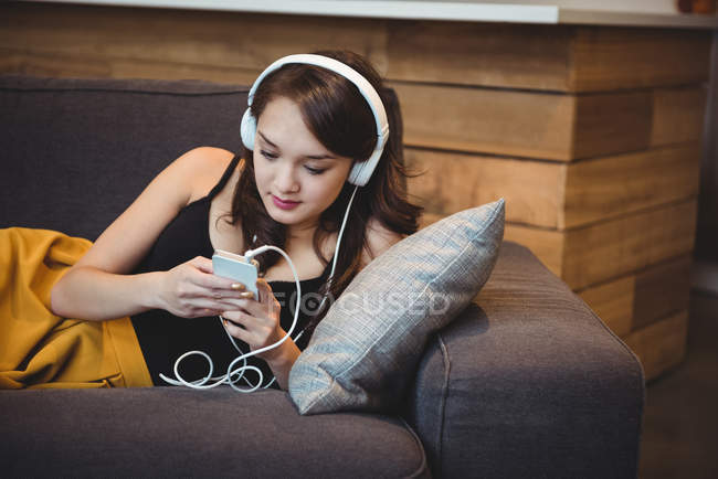 Frau liegt auf Sofa, während sie zu Hause mit Handy Musik hört — Stockfoto