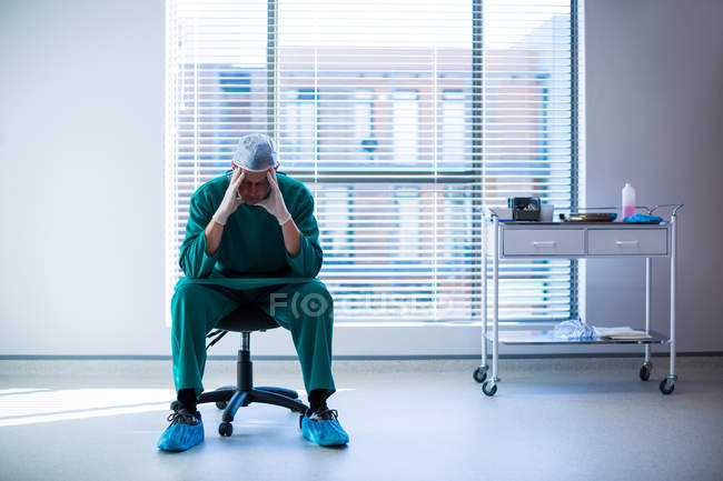 Tensed surgeon sitting on a chair in the hospital corridor — Stock Photo