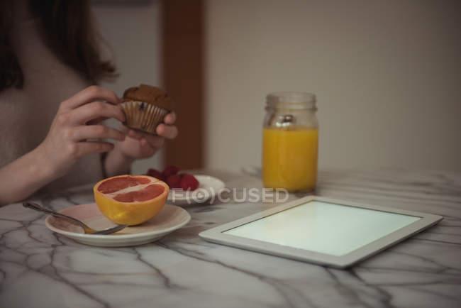 Partie médiane de la femme déballer cupcake tout en prenant le petit déjeuner à la maison — Photo de stock