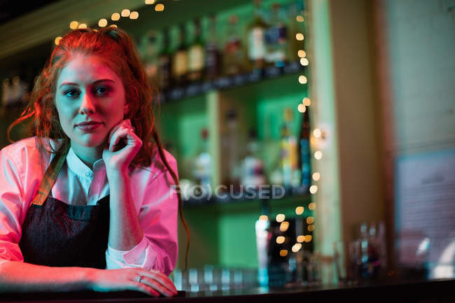 Portrait of a female bartender leaning on the bar counter — Stock Photo