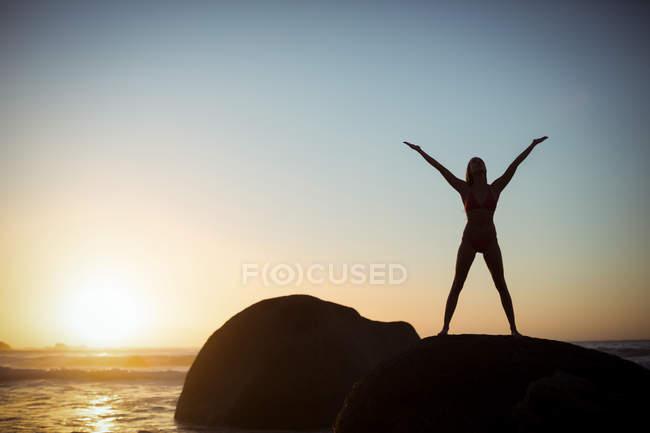 Жінка виконує розтяжку вправи на пляжі під час заходу сонця — стокове фото