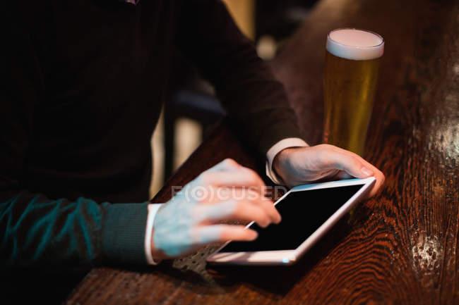 Mann benutzt digitales Tablet mit Bierglas auf Theke in Bar — Stockfoto