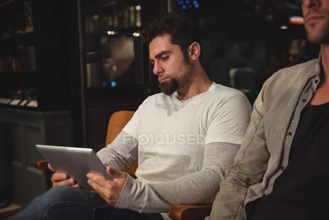Cliente usando tableta digital mientras espera en la peluquería - foto de stock