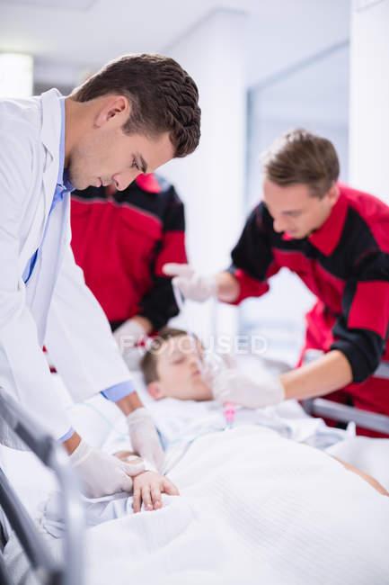 Médecins ajuster masque à oxygène tout en précipitant le patient dans les urgences à l'hôpital — Photo de stock