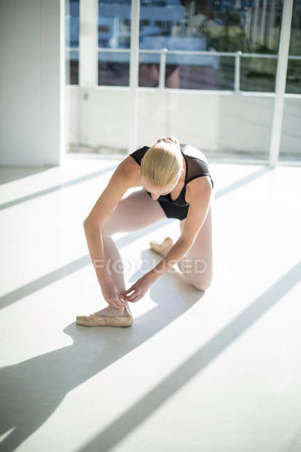Ballerina wearing ballet shoes in dance studio — Stock Photo