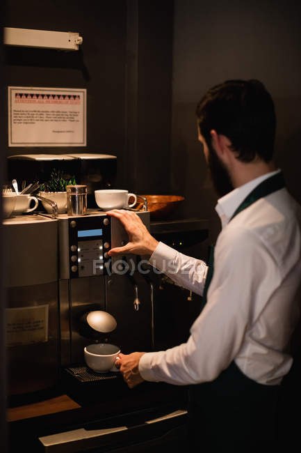 Waiter making cup of coffee from espresso machine in bar — Stock Photo