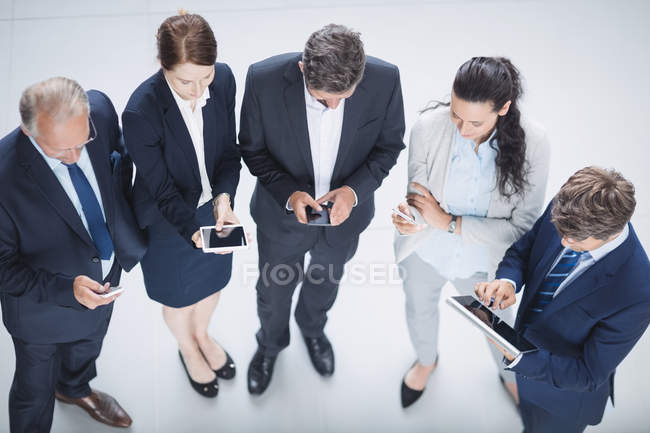 Overhead view of business people using mobile phone and digital tablet in office — Stock Photo
