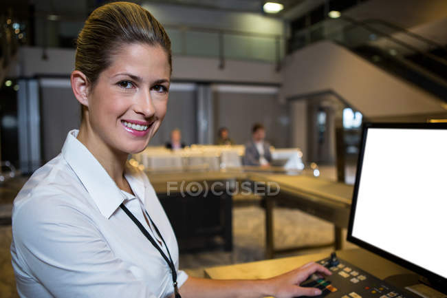 Portrait of female staff working in airport terminal — Stock Photo
