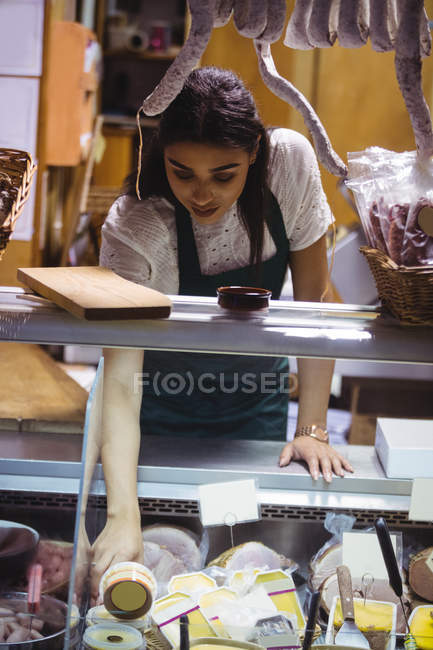 Female staff working at meat counter in supermarket — Stock Photo