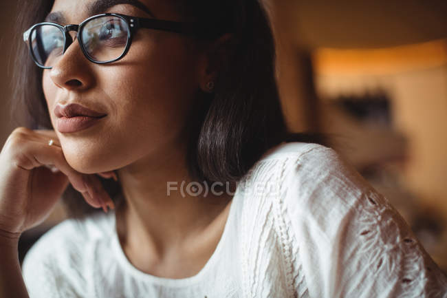 Thoughtful woman sitting with hand on chin in cafe — Stock Photo