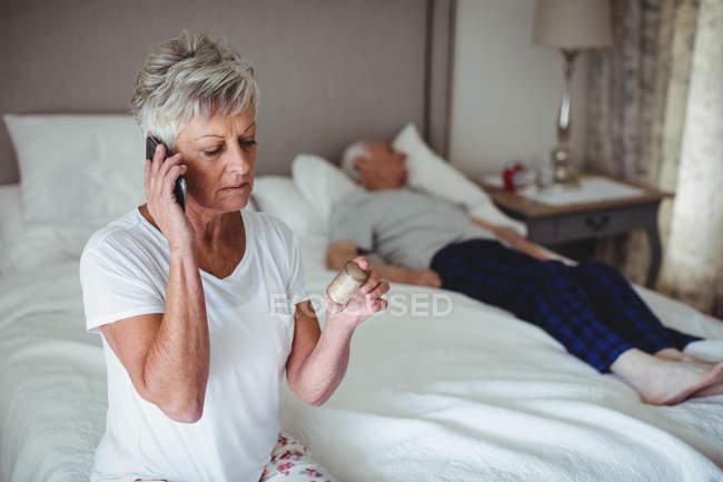 Femme âgée inquiète assise dans la chambre à coucher tenant la médecine et parlant sur un téléphone mobile — Photo de stock
