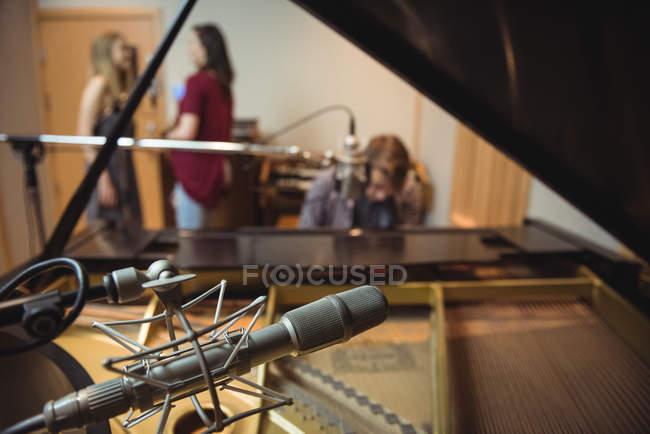 Крупный план микрофона в студии звукозаписи с музыкантами на заднем плане — стоковое фото