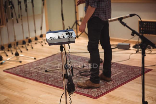 Baixa seção de homem de pé no estúdio de música — Fotografia de Stock