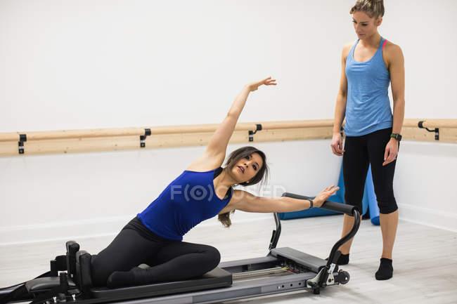 Женщина-тренер помогает женщине с упражнениями на растяжку на реформаторе в тренажерном зале — стоковое фото