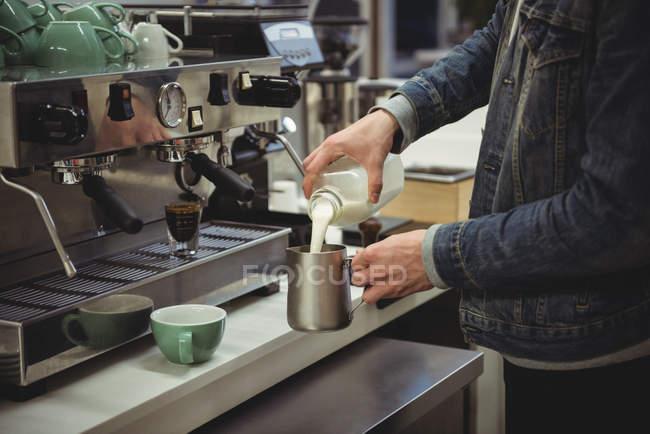 Розділ середині людина розливом молока в спінювання глечик в кафе — стокове фото