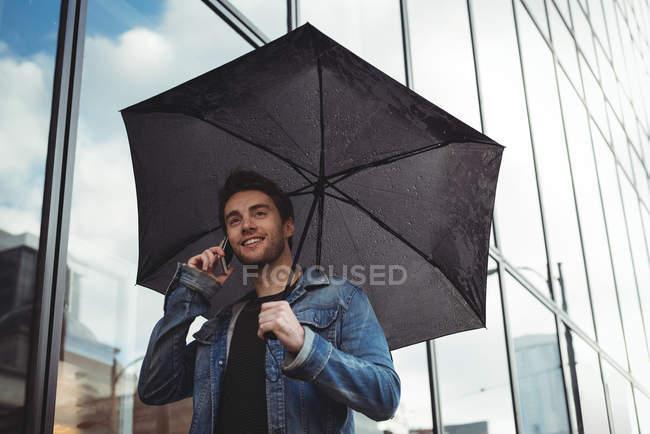 Hombre sosteniendo paraguas y hablando por teléfono móvil mientras camina por la calle — Stock Photo