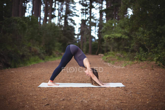 Woman performing yoga on exercise mat in forest — Stock Photo