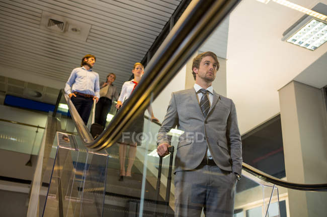 Passengers with luggage standing on escalator in airport — Stock Photo