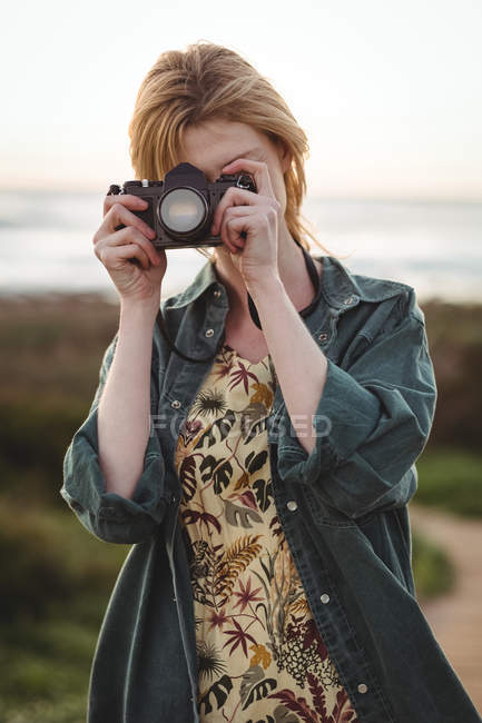 Woman taking photographs with digital camera on a sunny day — Stock Photo