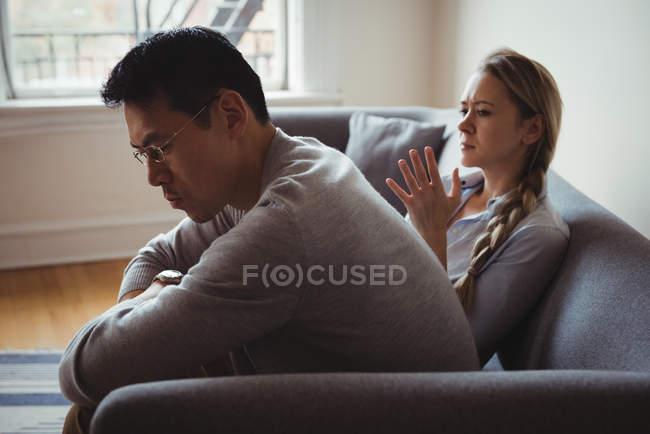 Couple malheureux se disputant dans le salon à la maison — Photo de stock