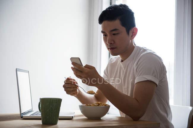 Mann benutzt Handy beim Frühstück zu Hause — Stockfoto