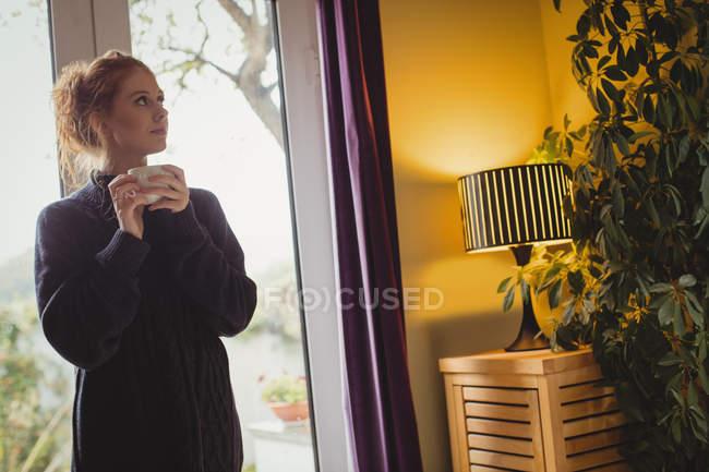 Продуманий жінка фотографіях хтось дивитися вбік маючи кави в домашніх умовах — стокове фото