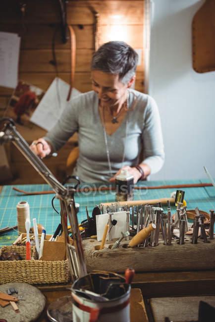 Attentive craftswoman working in workshop interior — Stock Photo