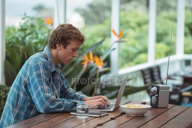 Mann sitzt am Tisch und benutzt Laptop zu Hause — Stockfoto