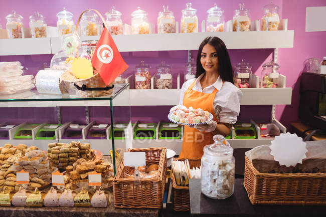 Portrait of female shopkeeper holding tray of turkish sweets at counter in shop — Stock Photo