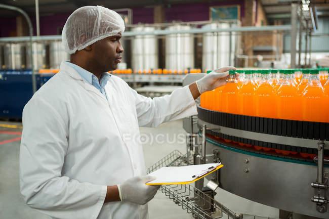 Серйозні чоловічого працівник вивчення пляшки сік заводі — стокове фото