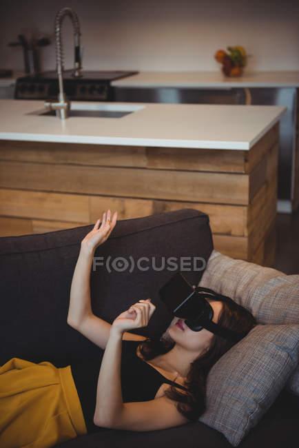 Mujer usando auriculares de realidad virtual mientras está acostada en el sofá en la sala de estar en casa - foto de stock