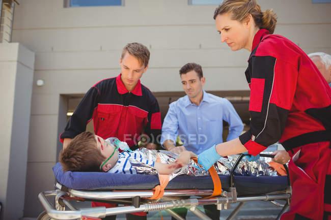Les ambulanciers examinent un garçon blessé dans la rue — Photo de stock