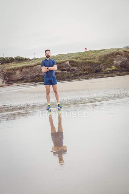 Спортсмен, стоя с руками, скрещенными на пляже — стоковое фото