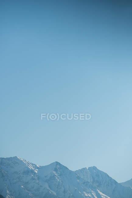Vue panoramique sur la chaîne de montagnes enneigée sur ciel bleu — Photo de stock