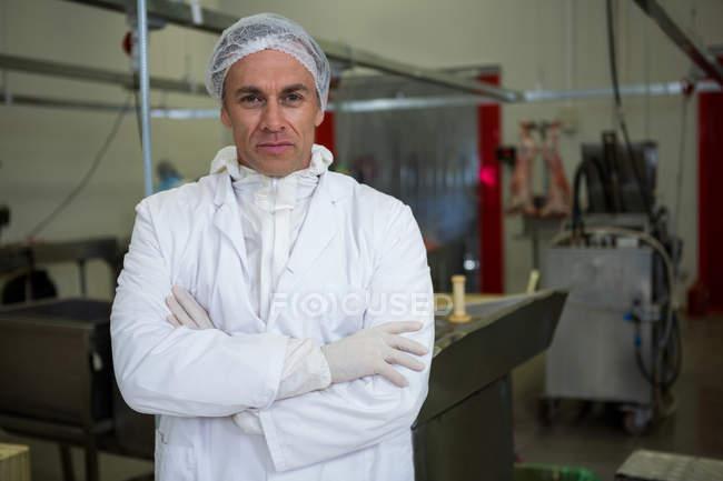 Портрет м'ясника з обіймами перетнула на заводі м'яса — стокове фото