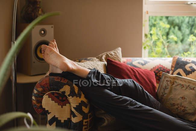 Femme couchée sur le canapé dans le salon à la maison — Photo de stock