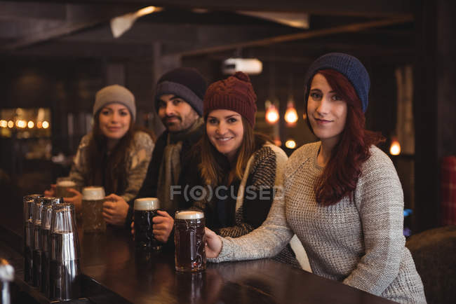 Portrait of friends holding beer glasses at bar counter — Stock Photo