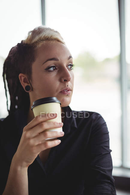 Woman holding disposable coffee cup in cafe — Stock Photo