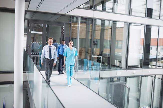 Médicos y enfermeras a pie en el pasillo del hospital - foto de stock
