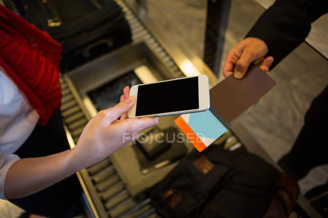 Close-up da fêmea digitalização de embarque com telefone móvel — Fotografia de Stock
