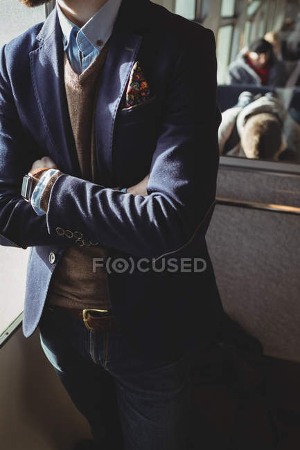 Mid-section of businessman standing with arms crossed in train — Stock Photo