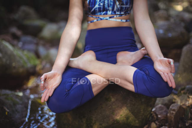 Woman meditating in lotus position in forest — Stock Photo