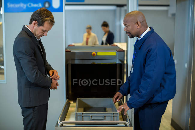 Airport security officer interacting with commuter in airport terminal — Stock Photo