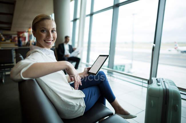 Портрет женщины-пригородницы с цифровой планшетом, сидящей в зале ожидания в аэропорту — стоковое фото