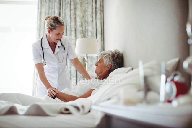 Ärztin interagiert mit Seniorin zu Hause — Stockfoto