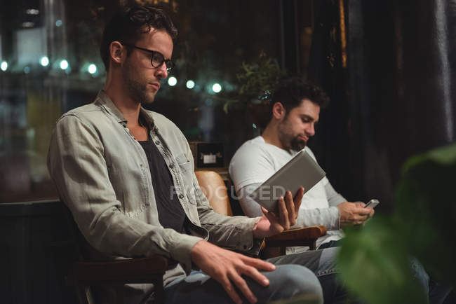 Clients using digital tablet and mobile phone while waiting in barber shop — Stock Photo