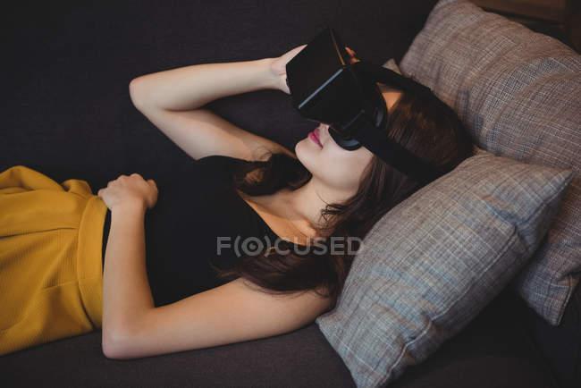 Femme utilisant casque de réalité virtuelle tout en étant couché sur le canapé dans le salon à la maison — Photo de stock