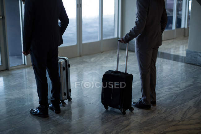 Business people with luggage standing at waiting area in airport — Stock Photo